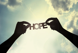 Hands holding the word hope to the sky