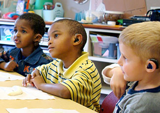 Three boys wearing hearing aids in a classroom