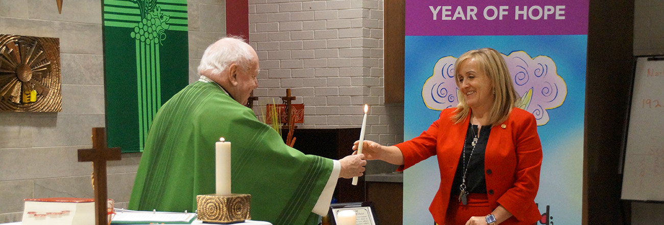 Father Keith Callaghan passing the candle to new Director of Education, Tracy Barill