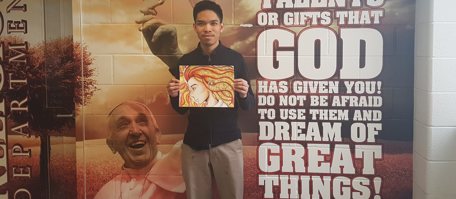 male student holding his award winning drawing for Stand Up to Bullying Week