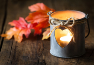 Tealight candle inside a candle holder with a cut out heart and fall leaves in the background
