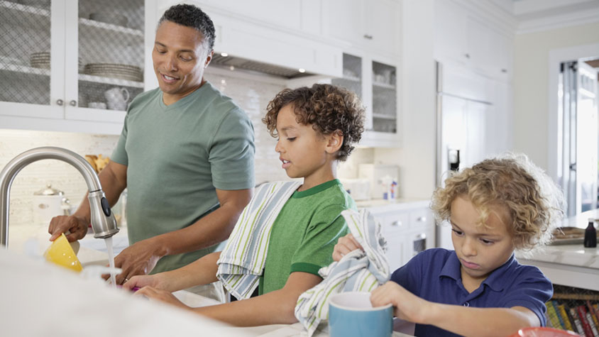 A man with two young boys washing and drying dishes