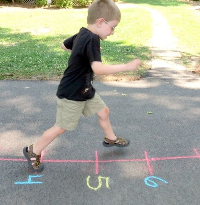 Young boy running on a chalk number line on a sidewalk