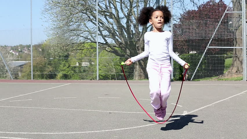 Young female girl skipping rope outside in a fenced in area