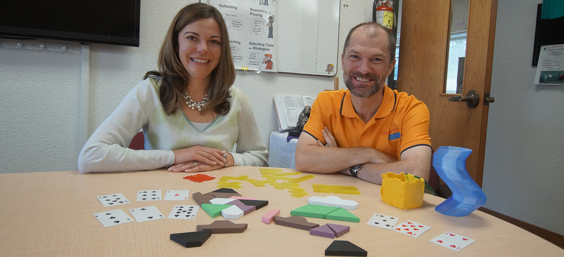Female and male adult sitting at a table with math items