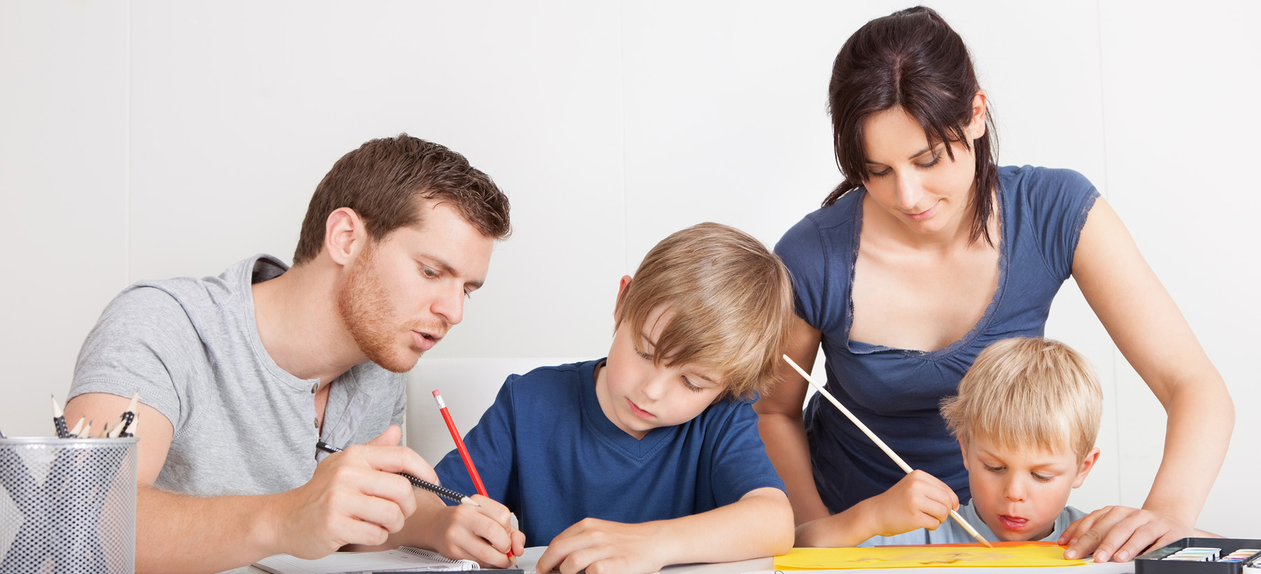 Male and female adult helping children with homework
