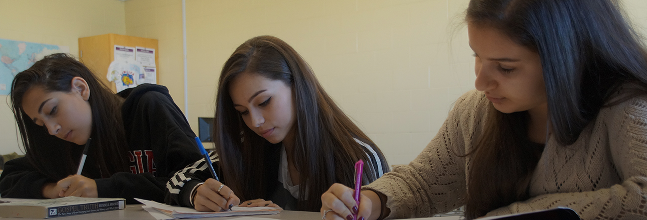 Three female students writing in a classroom