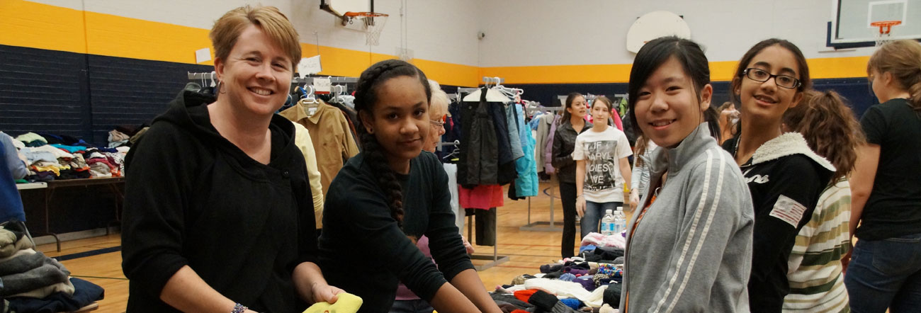 Students and teacher volunteer at a clothing drive