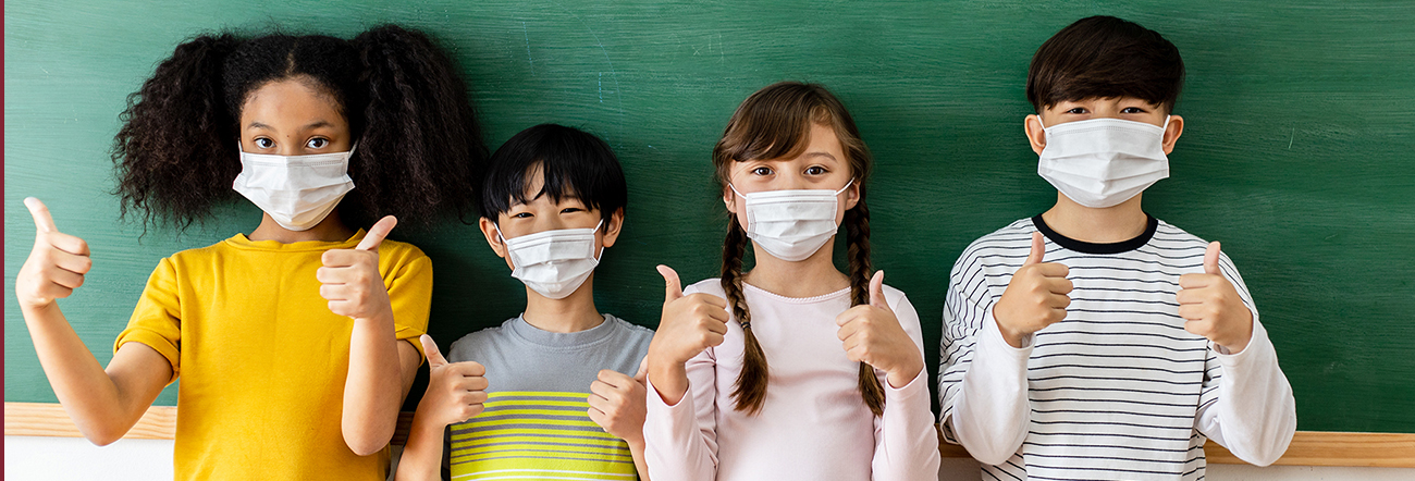 Four students wearing masks and giving a thumbs up