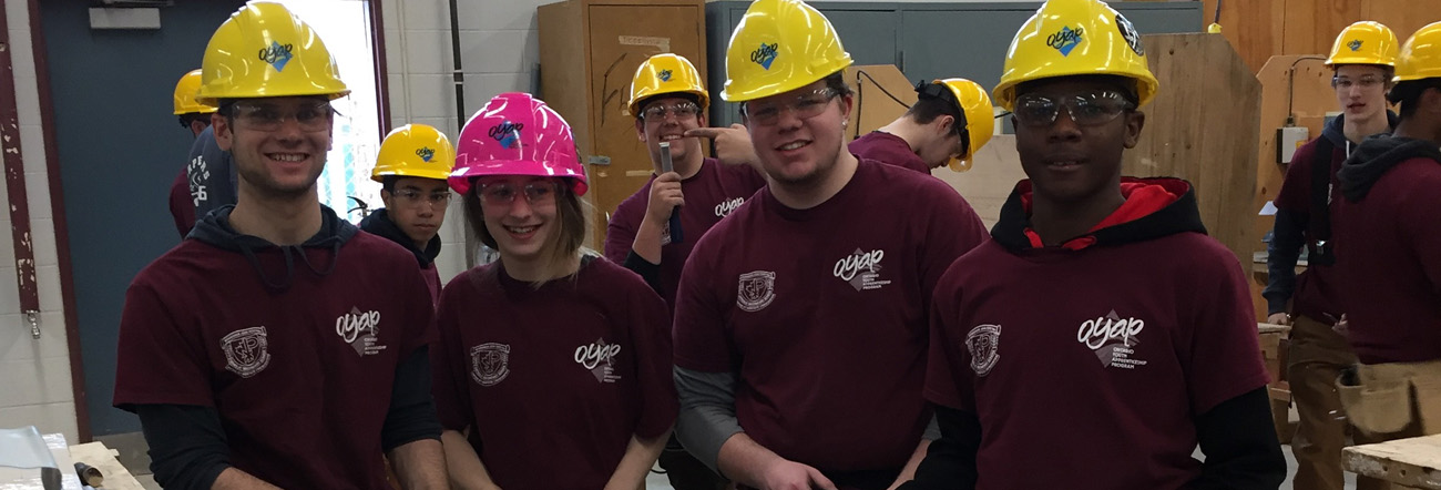Male students wearing yellow hard hats and one female student wearing a pink hard hat in a construction classroom